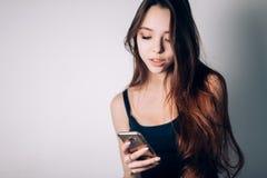 Mensaje que mecanografía hermoso de la mujer joven en el teléfono elegante Tecnología, Internet Fotografía de archivo libre de regalías