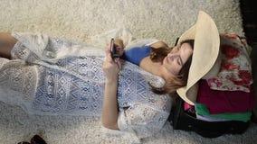 Mensaje que mecanografía relajado de la mujer joven en smartphone almacen de metraje de vídeo