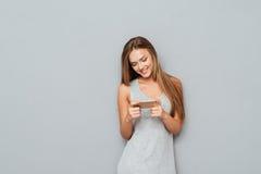 Mensaje que mecanografía sonriente de la muchacha hermosa de los jóvenes en smartphone Fotos de archivo libres de regalías