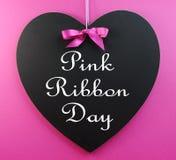 Mensaje rosado del día de la cinta escrito en una pizarra de la dimensión de una variable del corazón Fotografía de archivo libre de regalías