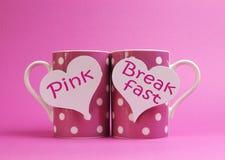 Mensaje rosado del desayuno escrito en dos tazas de café rosadas del lunar Imagen de archivo libre de regalías