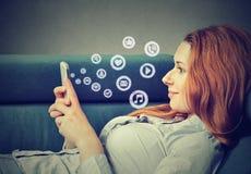 Mensaje sonriente de la lectura de la mujer en iconos sociales del teléfono los medios que vuelan del teléfono móvil Foto de archivo libre de regalías