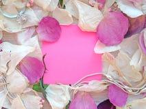 Mensaje vac?o en nota pegajosa rosada con los p?talos secos de la flor de la rosa y de la orqu?dea y el anillo y la cadena de la  fotografía de archivo libre de regalías