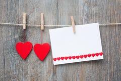 Mensaje y corazones rojos en la cuerda para tender la ropa fotos de archivo