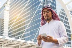 Mensajería árabe del hombre de negocios en un teléfono móvil en la ciudad Fotos de archivo libres de regalías