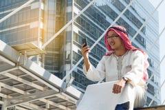 Mensajería árabe del hombre de negocios en un teléfono móvil en la ciudad Imagen de archivo