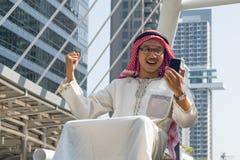 Mensajería árabe del hombre de negocios en un teléfono móvil en la ciudad Fotos de archivo