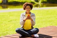 Mensajería africana feliz de la mujer joven en smartphone Imagenes de archivo