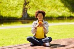 Mensajería africana feliz de la mujer joven en smartphone Foto de archivo