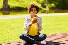 Mensajería africana feliz de la mujer joven en smartphone Imagen de archivo