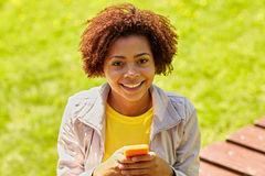 Mensajería africana feliz de la mujer joven en smartphone Fotos de archivo libres de regalías