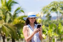 Mensajería de la mujer joven con el teléfono elegante de la célula sobre la muchacha morena tropical de Forest And Blue Sky Beaut Fotos de archivo