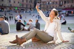 Mensajería de la mujer joven/usando el app en su Smart-teléfono Fotos de archivo