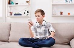 Mensajería del adolescente en línea en smartphone en sala de estar en casa Imágenes de archivo libres de regalías