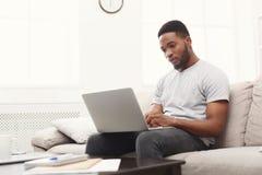 Mensajería del hombre joven en casa en línea en el ordenador portátil imagen de archivo libre de regalías