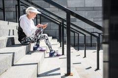 Mensajería envejecida concentrada de la señora a través de su teléfono móvil en los pasos de piedra Imágenes de archivo libres de regalías