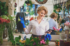 Mensajería femenina alegre del florista en el teléfono móvil Foto de archivo libre de regalías