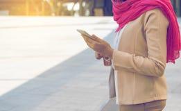 Mensajería musulmán de la mujer en un teléfono móvil Fotografía de archivo libre de regalías