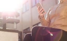 Mensajería urbana joven de la mujer con smartphone en puesta del sol o salida del sol Forma de vida moderna Fotos de archivo