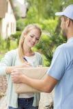 Mensajero con el cliente joven feliz que firma un impreso de entrega fotos de archivo libres de regalías