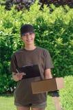 Mensajero de sexo femenino sonriente que entrega un paquete Imágenes de archivo libres de regalías