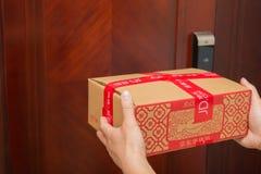 Mensajero de sexo masculino de JD COM que entrega un paquete con cosas chinas del Año Nuevo Imágenes de archivo libres de regalías