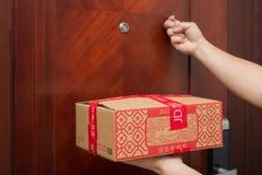 Mensajero de sexo masculino de JD COM que entrega un paquete con cosas chinas del Año Nuevo y que golpea la puerta Fotos de archivo