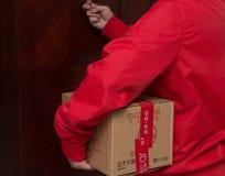Mensajero de sexo masculino de JD COM que entrega un paquete por días en línea de las compras Fotografía de archivo libre de regalías
