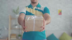 Mensajero de sexo masculino mustachioed joven del hombre de entrega con la caja de regalo a disposici?n almacen de video