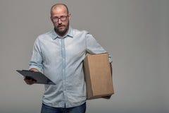 Mensajero de sexo masculino sonriente que entrega un paquete imágenes de archivo libres de regalías