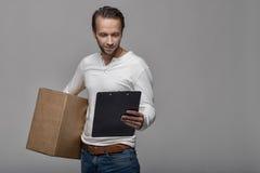 Mensajero de sexo masculino sonriente que entrega un paquete imagenes de archivo