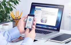 Mensajero del telegrama en la pantalla del iPhone en las manos masculinas y la versión de escritorio del telegrama en macbook Imágenes de archivo libres de regalías