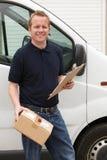 Mensajero Delivering Package Standing al lado de Van Imagenes de archivo