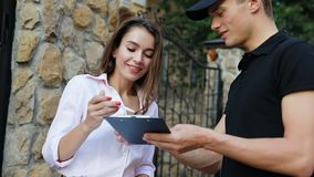 Mensajero Delivering Pizza Mujer que recibe el paquete de la comida cerca de hogar almacen de video