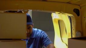 Mensajero en cajas azules de las cargas uniformes en el coche Tirado desde adentro de un coche almacen de video