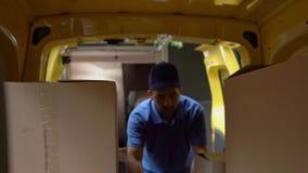 Mensajero en cajas azules de las cargas uniformes en el coche Tirado desde adentro de un coche almacen de metraje de vídeo