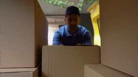 Mensajero en cajas azules de las cargas uniformes en el coche Tirado desde adentro de un coche metrajes