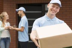 Mensajero en el uniforme azul que celebra el paquete y la sonrisa marrones grandes fotografía de archivo