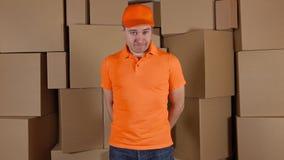 Mensajero en paquete dañado de entrega uniforme de la naranja al cliente Brown encuadierna el fondo Defecto y trabajo no profesio metrajes