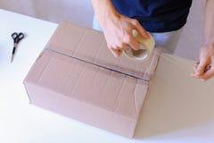 Mensajero Manstanding en la oficina de correos, caja de Brown de la cinta del pegamento en todo el S Imagenes de archivo