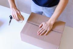 Mensajero Manstanding en la oficina de correos, caja de Brown de la cinta del pegamento en todo el S Imágenes de archivo libres de regalías