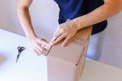 Mensajero Manstanding en la oficina de correos, caja de Brown de la cinta del pegamento en todo el S Foto de archivo libre de regalías