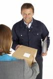Mensajero que entrega el paquete a la empresaria Fotos de archivo libres de regalías