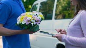 Mensajero que entrega las flores mujer, firma de la tableta, cuidado de la familia del presente de cumpleaños metrajes