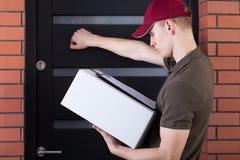 Mensajero que golpea en la puerta del cliente Imagen de archivo libre de regalías
