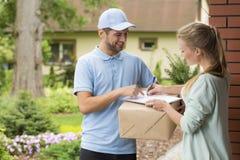 Mensajero que sostiene un paquete y mujer que firma un impreso de entrega Fotografía de archivo libre de regalías