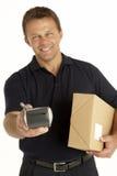 Mensajero que sostiene un paquete y un sujetapapeles electrónico Imagen de archivo libre de regalías