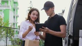 Mensajero Service de la entrega Hombre que entrega el paquete a la mujer almacen de video