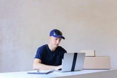 Mensajero Sitting en el escritorio, mecanografiando en el ordenador en la oficina de correos Imagen de archivo libre de regalías
