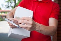 Mensajero usando la tableta en el trabajo imagen de archivo libre de regalías